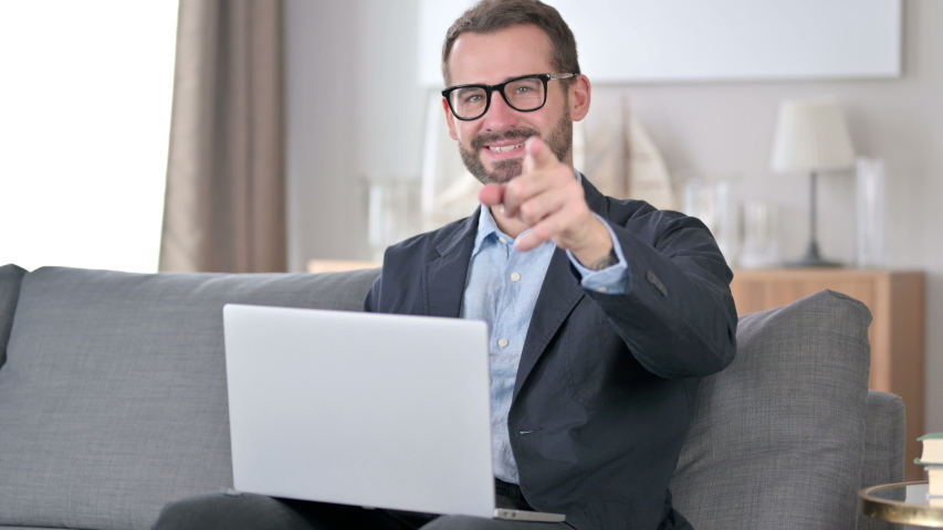 Young Businessman with Laptop Pointing with Finger at Home | Shutterstock HD Video #1054722665