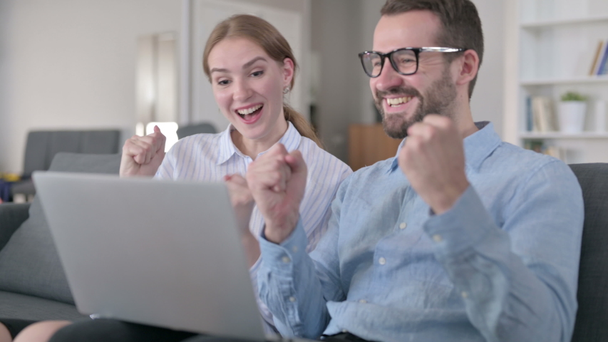 Excited Young Couple Celebrating Success on Laptop at Home    Shutterstock HD Video #1054722671