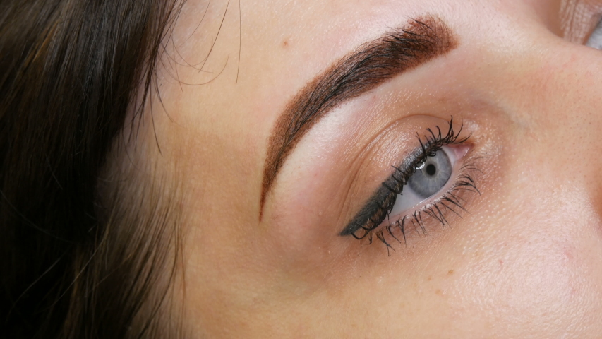 The face portrait of a beautiful young woman with blue eyes and long eyelashes after the procedure of permanent make up by microblading with eyebrow tattoo lies on a couch in a beauty salon close up. | Shutterstock HD Video #1054722818