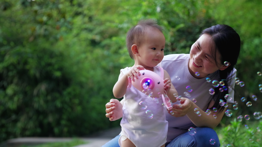 Slow motion of happy little asian baby girl playing soap bubble together with her mother outdoor in the park adorable one year old baby lifestyle footage