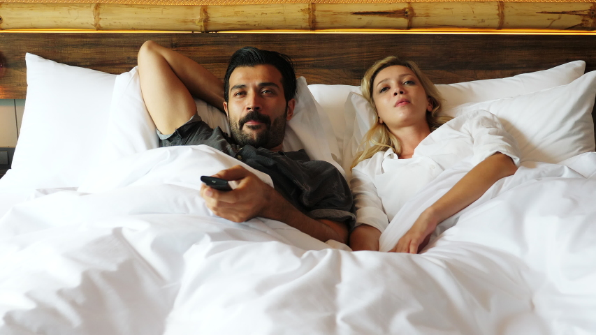 Couple watching television together on bed Husband change to favorite channel wife don't want to watch it and snatch remote control tv from husband, changing her favorite program that make guy angry