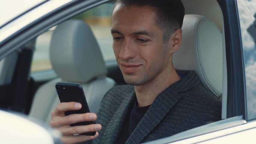 Portrait of smiling male businessman sitting at the wheel of a car and using smartphone. | Shutterstock HD Video #1054723745