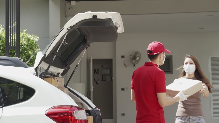 Asian deliver man wearing face mask in red uniform handling parcel box give to woman customer walking come in front of the house. Postman and express grocery delivery service during covid19.