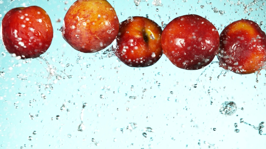 Super slow motion of falling peaches with water splashes. Filmed on high speed cinema camera, 1000fps