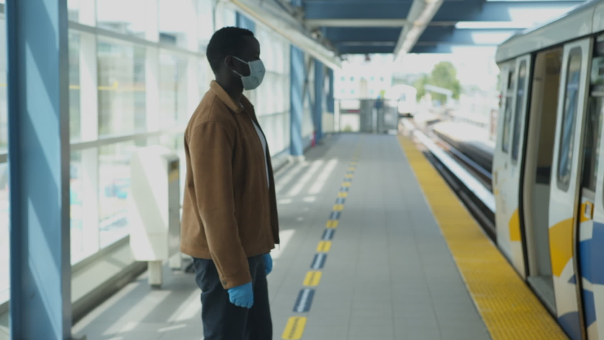 African American black man wearing PPE mask and gloves on public transportation train, walks on and sits down, camera tracks through door to follow. 4K daylight. | Shutterstock HD Video #1054724351