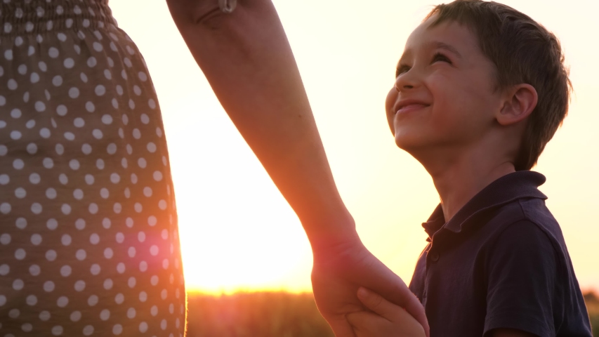 Mother walks with her son holding hands at sunset. A cute little child holds his mother's hand and looks at her experiencing emotions of happiness, a smile. The concept of a happy family and family   Shutterstock HD Video #1054724804