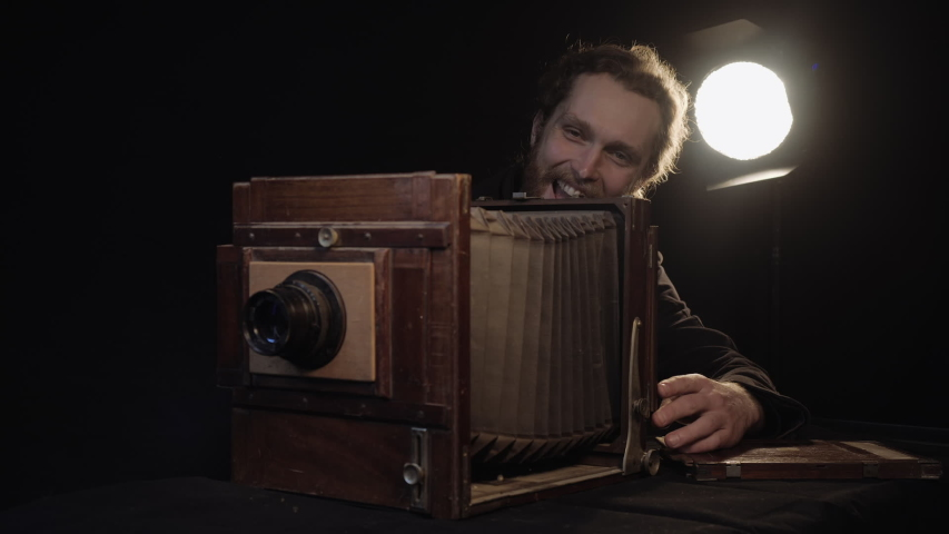 Close-up view of old rare antique camera, restored and repaired by bearded active man in dark isolated studio room against background of luminous lamp. Inspection obsolete old style retro technician.