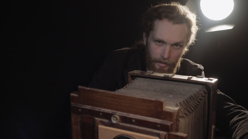 Bearded man carefully restores old retro photo equipment, adjusts lens, looks at wooden camera with smile enjoys repair spreading hands in pleasure. Repair antique obsolete camera in isolated room. | Shutterstock HD Video #1054725098