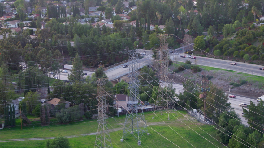 Aerial, drone shot, over wires, towards traffic on a highway, on a sunny evening, in Los Angeles, California, USA | Shutterstock HD Video #1054725209