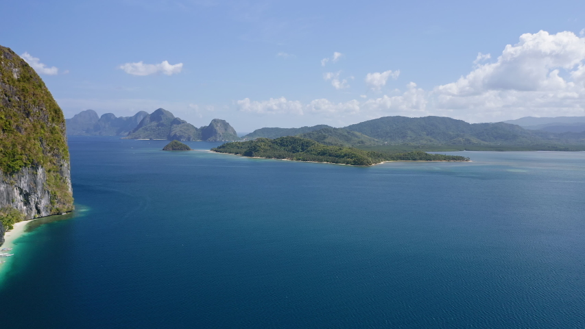 4K Aerial drone fly over ocean towards a El Nido mainland with towering limestone karst mountain ridge covered by jungle in background. | Shutterstock HD Video #1054725233