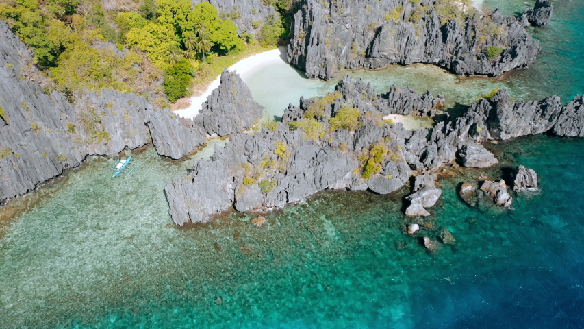 Aerial drone view lonely tourist boat at Hidden beach on Matinloc Island in El Nido, Palawan, Philippines - Tour C route - Paradise lagoon in tropical scenery. | Shutterstock HD Video #1054725236