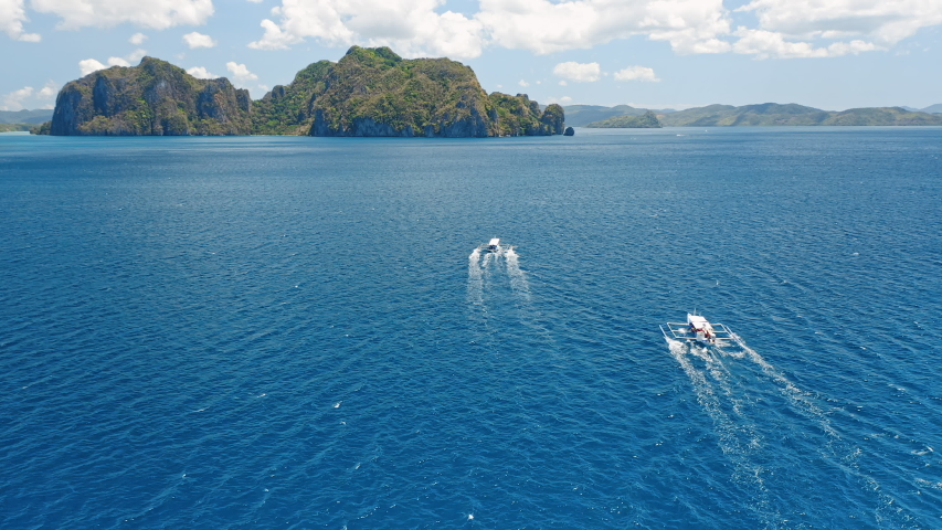 El Nido, Palawan island, Philippines. Aerial drone follow for tourist banca boating in open sea with beautiful islands.