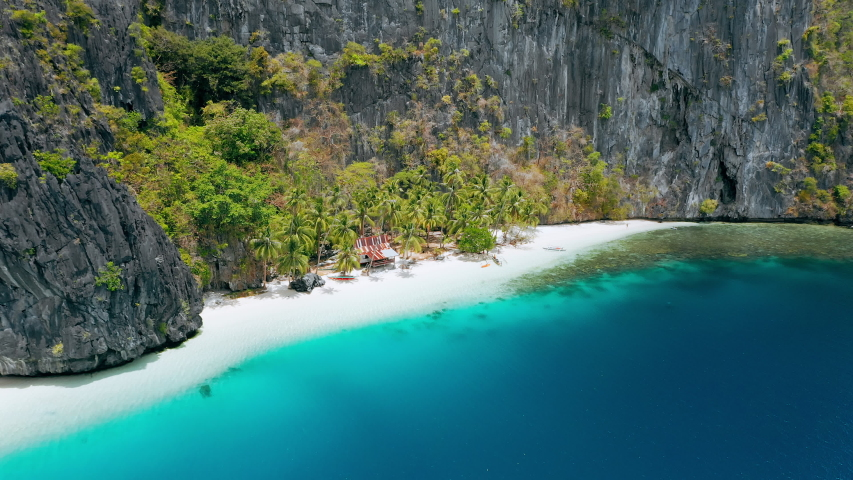 Paradise tropical hidden isolated sandy Beach with local hut on Pinagbuyutan island. El Nido, Palawan, Philippines. Crystal pure turquoise water, coconut palm trees and amazing white sand beach. | Shutterstock HD Video #1054725245