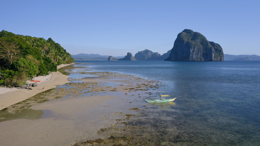 4k Aerial view of El Nido, Palawan, Philippines. Banca boat moored in shallow water during low tide. Tropical beach with island in background.
