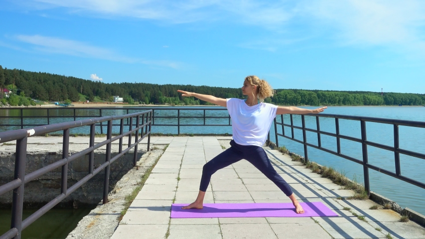 Young woman practicing yoga, standing in warrior and triangle yoga poses at a pier near the sea. | Shutterstock HD Video #1054725263