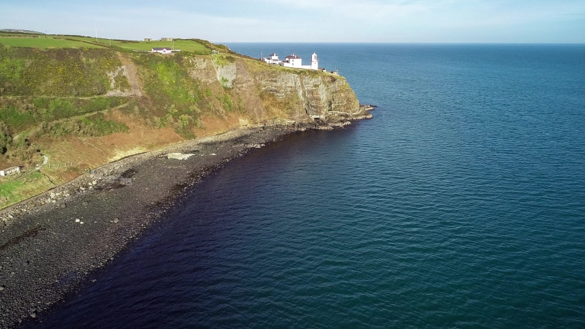 Blackhead Lighthouse in Whitehead village near Carrickfergus and Belfast on a steep cliff with coastal walking path on the Atlantic coast in County Antrim, Northern Ireland, UK. Aerial  4K video   Shutterstock HD Video #1054725335