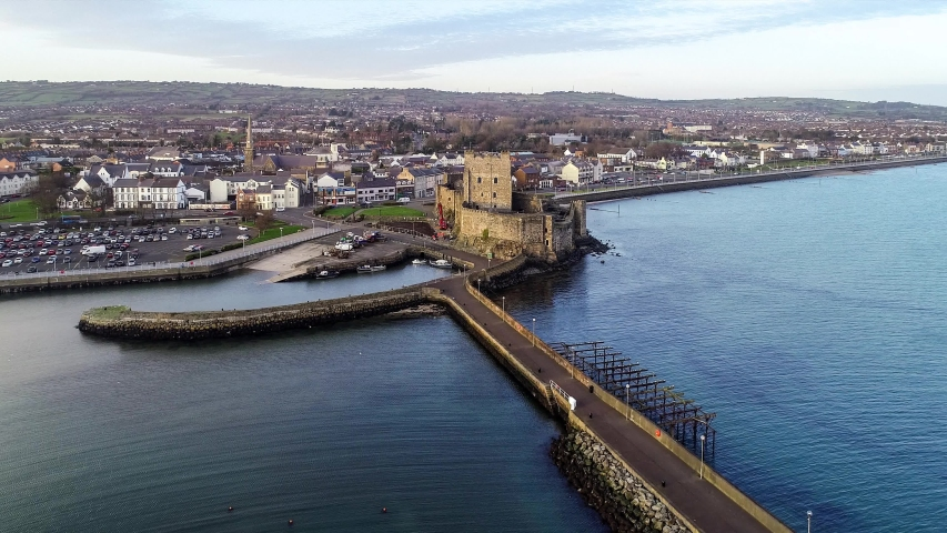 Medieval Norman Castle and harbor in Carrickfergus near Belfast in sunset light. Aerial 4K approaching video with  marina, yachts, boat ramp, breakwater  town, parking lot and traffic | Shutterstock HD Video #1054725338