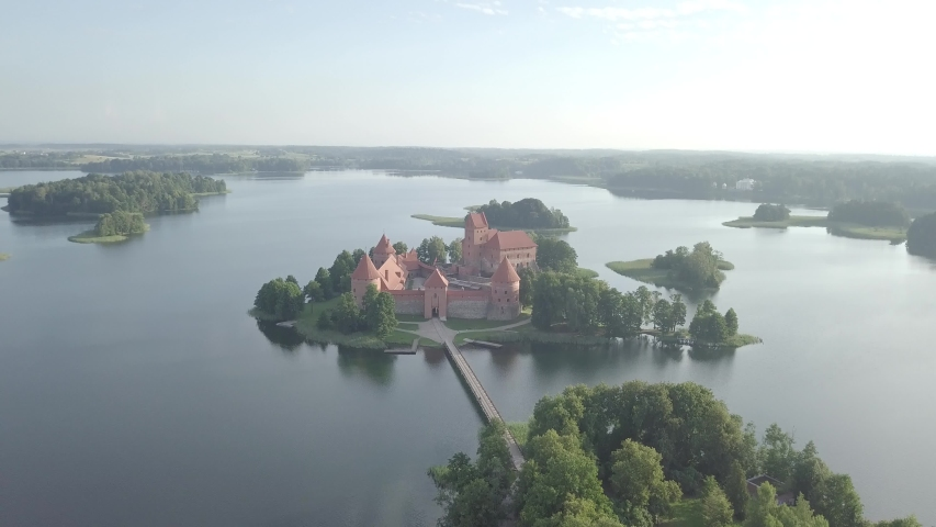 Aerial panning up view of Medieval Trakai castle on green island in Galve lake, early morning sunrise. Lithuania popular historic landmarks. Europe UNESCO world heritage site. Drone goes up.