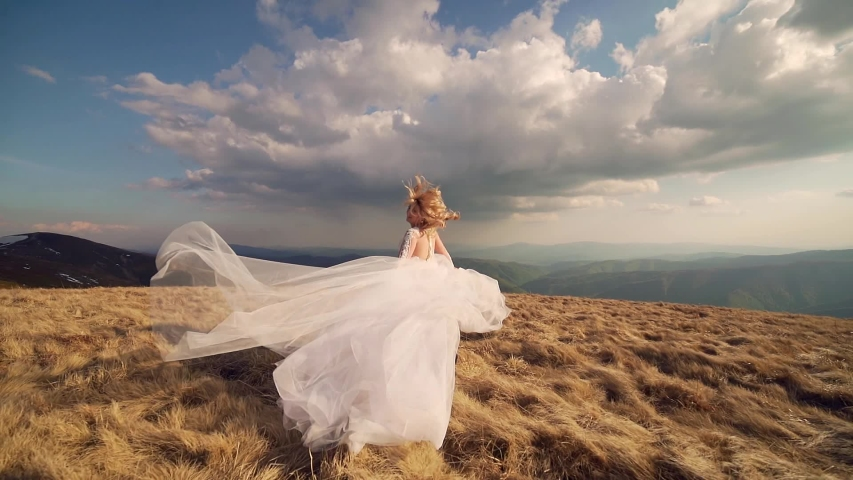 Attractive young bride with white hair in a wedding dress walks or runs on the mountain, ha background of mountains and rocks landscape, dramatic sky. slow motion | Shutterstock HD Video #1054725575