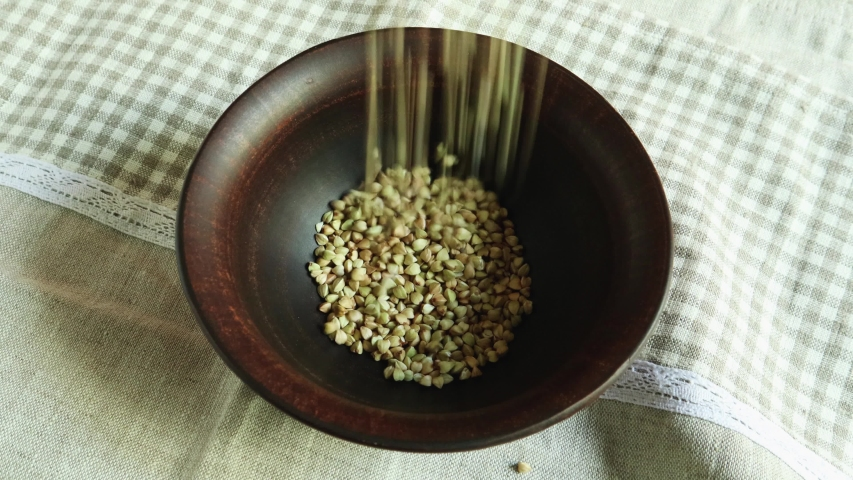 Pour raw green buckwheat into a plate. Fresh green buckwheat kernels fall into a clay brown bowl, close-up. Raw Healthy Organic Diet. The concept of healthy vegetarian eco food, diet | Shutterstock HD Video #1054725812