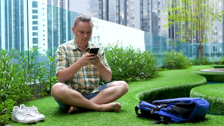 Freelancer or student man in plaid green shirt uses smartphone on green grass on cityscape building background. Wake up to bare feet, blue backpack