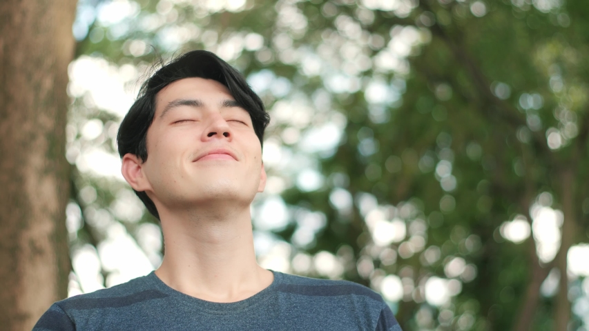 Asian handsome man taking deep breath, Young mixed race man relaxing breathing in fresh crisp air in green background. Stop and smell the tree, connect with nature. Royalty-Free Stock Footage #1054726235