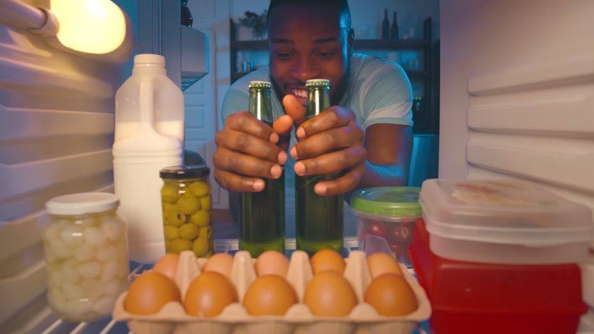 View from fridge of afro-american young guy taking two bottles of beer from refrigerator at night time. Afro man breaking diet taking beer in fridge at nighttime