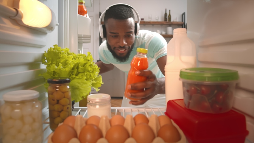 View from fridge of young afro-american guy in headphones taking bottle of carrot juice from refrigerator at home kitchen. Man taking juice from fridge to fresh up