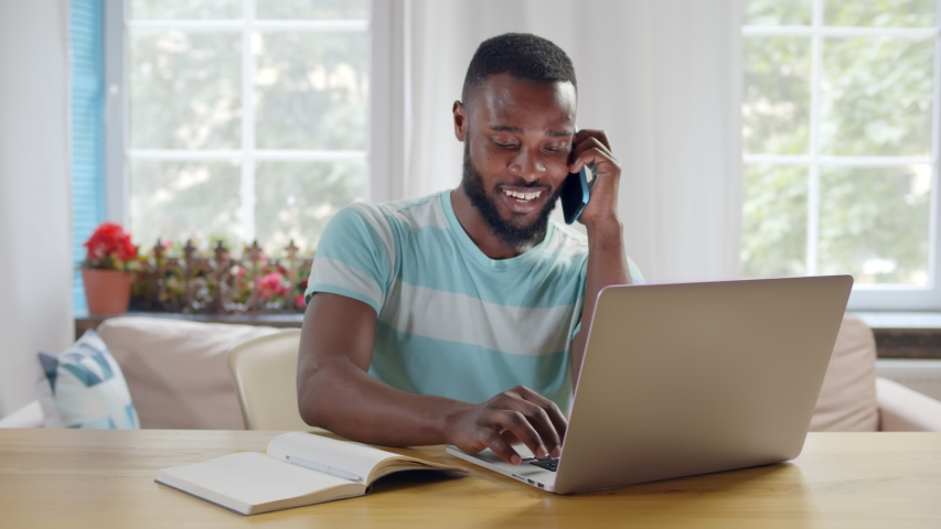 Portrait of afro-american businessman talking on phone with client looking at laptop screen and discussing new startup project working from home office Royalty-Free Stock Footage #1054726316