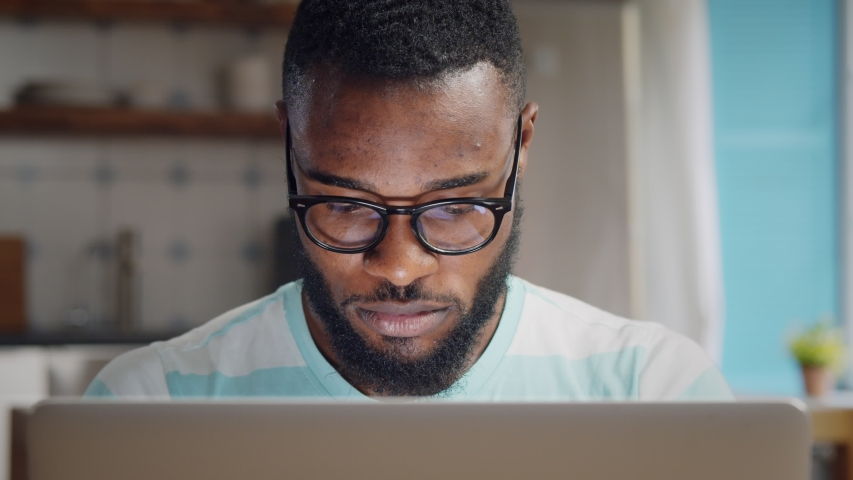 Young african freelancer man working on computer at home. Casual concentrated entrepreneur developing new project while working on laptop at home. Royalty-Free Stock Footage #1054726322
