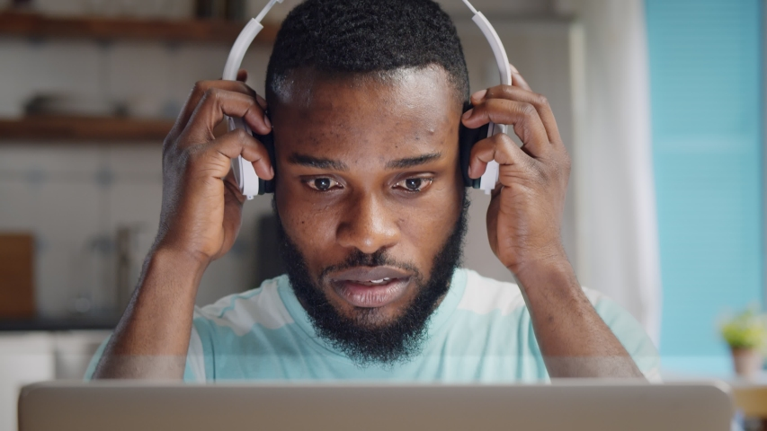 Close up of concentrated young african man in headphones with laptop computer working at home office. Remote job, technology and people concept Royalty-Free Stock Footage #1054726355