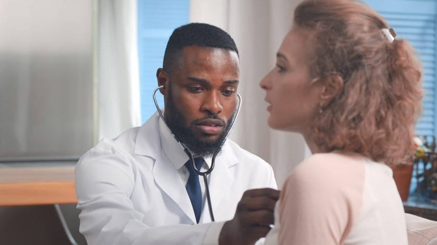 Young Afro-american Doctor Checking Patient at Home. Practitioner Checking Heartbeat of Female Patient Using Stethoscope. Doctor Doing Home Service.
