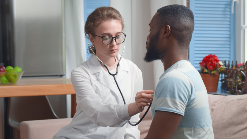 Portrait of pretty young woman doctor using stethoscope examining patient health during visit at home. Physician consulting and treating afro-american man at home