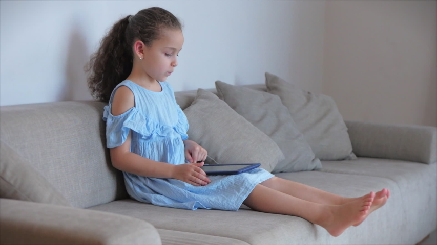 Happy Little Girl or child playing at home relaxing use a smartphone cuddling sit on sofa daughter and son,look at the screen of a cell phone, watch cartoons.