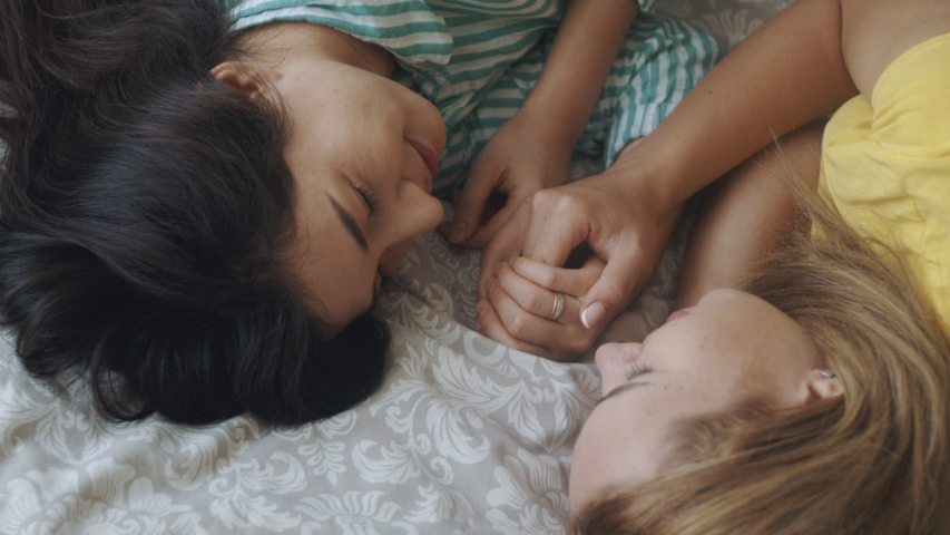 Homosexual mixed race lesbian couple lying on bed, looking each other. Two women sharing love and support holding hands. Gay family. LGBTQI, Pride Event, LGBT Pride Month, friendship concept.