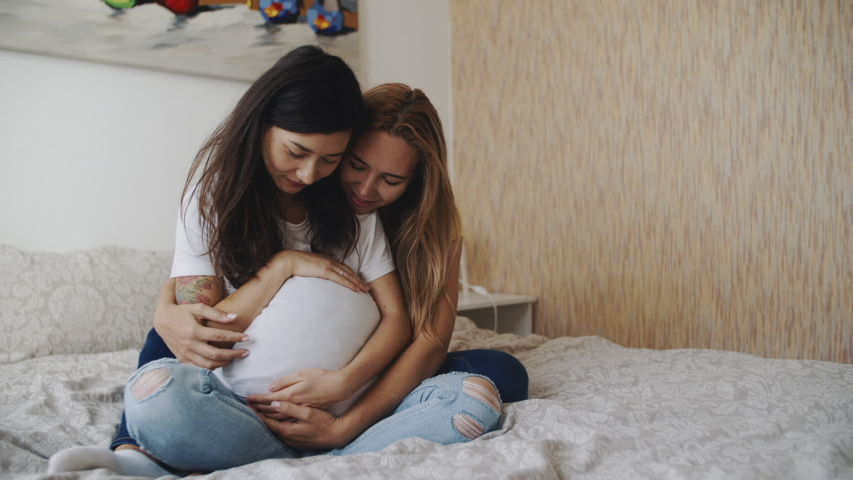 Portrait of happy lgbt lesbian family expecting a baby. Mixed race women in love, petting a big belly. Happiness of motherhood. IVF, LGBTQI, LGBT Pride Month, relationship, childbirth concept.