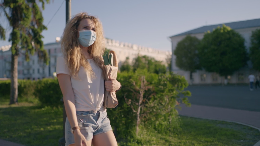 Pandemic shopping. Social distance for prevent outbreak. Another life after quarantine. Young woman in protective mask and gloves carries bag with products from store to home. Covid effect concept.   Shutterstock HD Video #1054726640