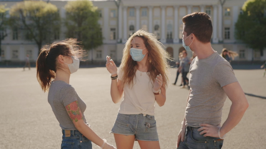Social distancing. Multiracial Friends in protective face mask greet their elbows. Elbow bump is new greeting to avoid spread of coronavirus or covid-19 - Avoid or Stop handshakes due to pandemic Royalty-Free Stock Footage #1054726646