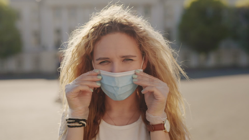 Put on your respirator to protect the other people. Pandemic coronavirus covid concept. Curly blond woman putting on surgical protective mask for corona virus second outbreak prevention. 6K Downscale Royalty-Free Stock Footage #1054726655