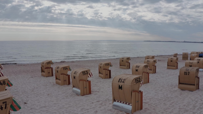 Evening seascape inspiring serenity and silence with spread beach chairs on a desolate beach under a cloudy sky | Shutterstock HD Video #1054726727