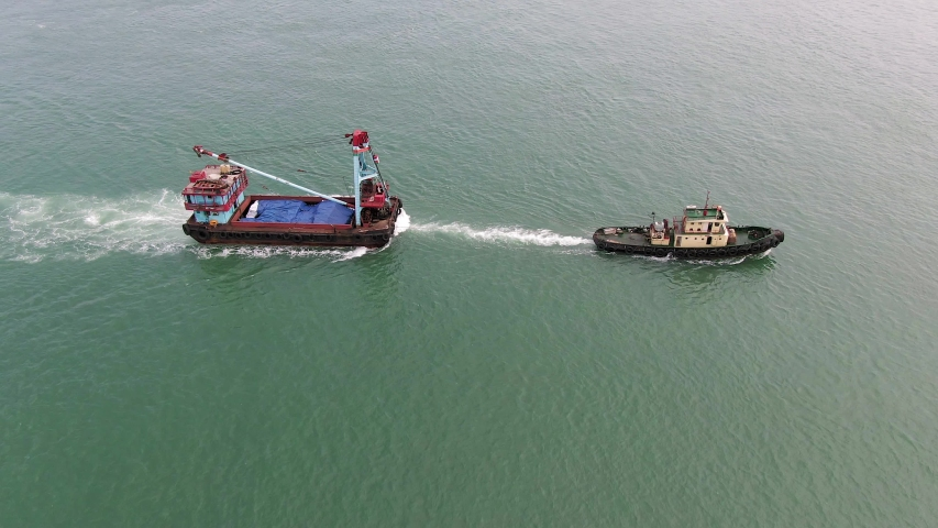 Tugboat pulling a small Barge in Hong Kong bay, Aerial view. | Shutterstock HD Video #1054726748