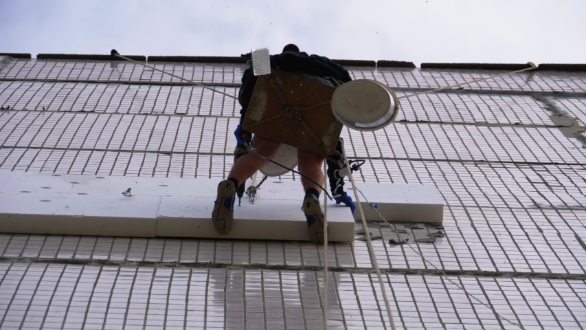 Industrial Climber Suspended on Ropes Performs Work on the Insulation of the Facade of Building with Foam. Warms an old panel high-rise multi-story residential building using Styrofoam. Bottom view | Shutterstock HD Video #1054726910