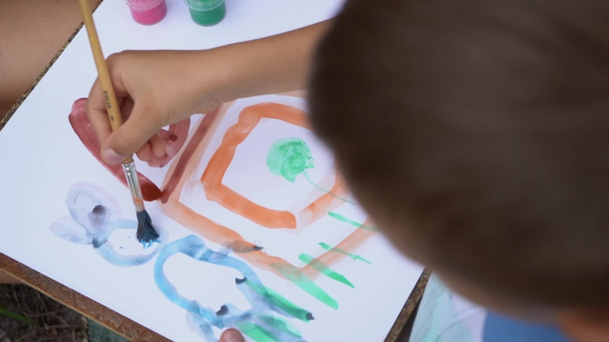 Closeup top view video footage of happy caucasian family of two people paints together sitting outdoors on ground. Mother helps and teaches her little 5 years old son to paint cute bunny face.   Shutterstock HD Video #1054727297
