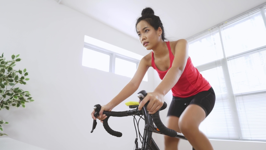 Asian woman cyclist. She is exercising in the house.By cycling on the trainer  Royalty-Free Stock Footage #1054727357