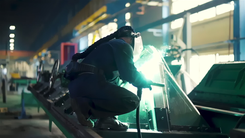 Factory Man at the Modern Rail Car Train Manufacture Welding the Huge Metal Structure Welder in Protective Mask Sparks Flash Light Comes From the Hose | Shutterstock HD Video #1054727420