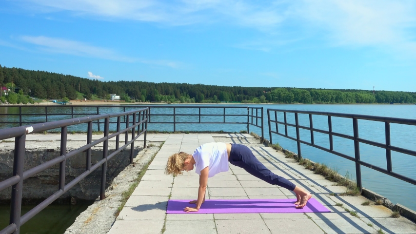 Woman practicing yoga at pier with a view on sea. Girl doing Sun salutation a sequence of yoga poses. | Shutterstock HD Video #1054727504
