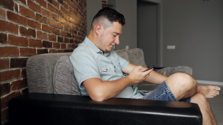 A man with a black smartphone in his hands sits on a sofa in a living room. He is angry and screams. A man is wearing summer jeans clothes. Backlight from the lamp | Shutterstock HD Video #1054727510
