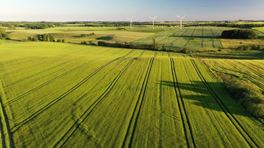Wind turbines that produce electricity, built on a field in Skanderborg, Denmark | Shutterstock HD Video #1054727729