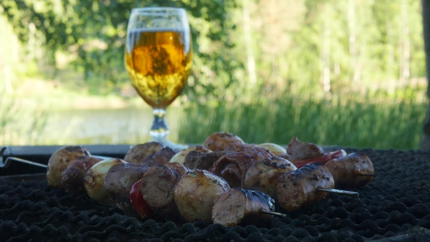 Meat and vegetables mixed together and put on a metal stick are being grilled over a hot coal bbq. In the background there is a lake and a newly poured lager beer on display. | Shutterstock HD Video #1054727744