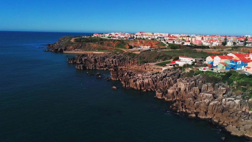 Traditional city on rocky peninsula near Atlantic ocean, aerial view showing village with white houses